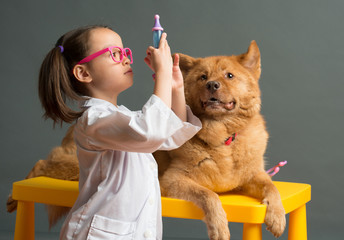 Girl holding a toy syringe and playing veterinarian with dog