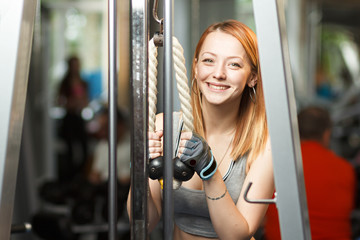 Concept: sport, healthy lifestyle. Young strong girl do exercises on cable crossover machine