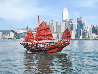 Foto op Aluminium Hong-Kong Hong Kong traditional red-sail Junk boat on city skyscrapers background