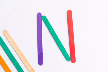 colorful of Ice cream sticks with word N on white background