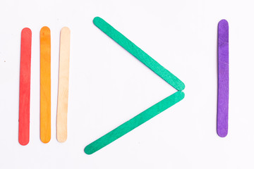 colorful of Ice cream sticks with greater than sign on white background