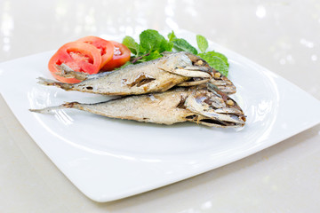 Fried mackerel with vegetable in white dish on tile plate