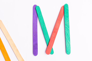 colorful of Ice cream sticks with word M on white background