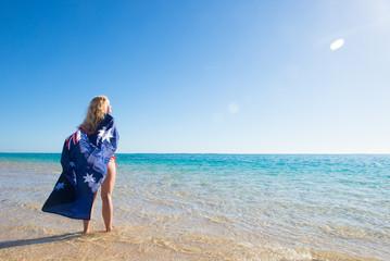 Happy woman Australian flag at beach