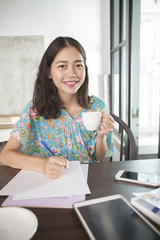 asian woman writing pen on white paper and hot beverage cup in h
