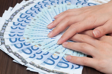 A woman is counting cash money, euro currency, dark background
