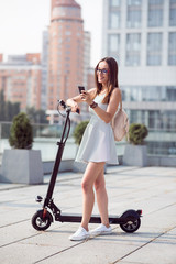 Delighted positive woman standing near kick scooter