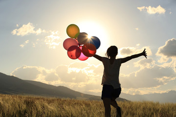 cheering young asian woman on grassland with colored balloons