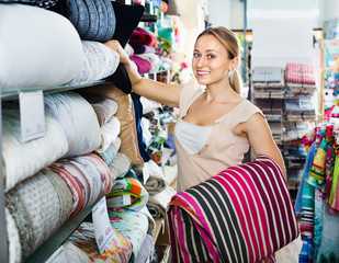 Youngwoman buying bed spread in  textile store