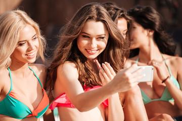 Four pretty young girls in bikinis making selfie