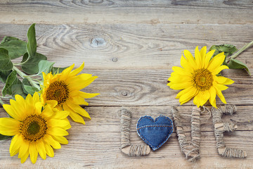Background with yellow sunflowers and the word love on old woode