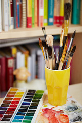 Photo of brushes in the glass and watercolors on blurred bookshe