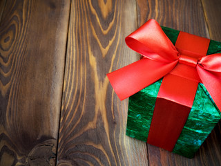 Green gift box on wooden board. Copy space. Holidays concept