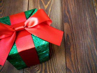 Gift box in glittery paper with bow on wooden board. Holidays concept