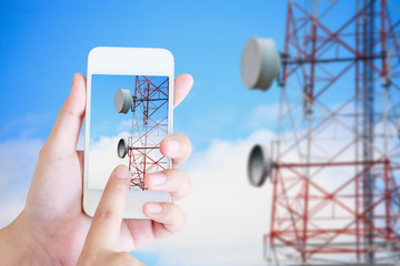 hand hold mobile smartphone with telecommunication tower