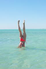 Sporty bikini woman handstand ocean water