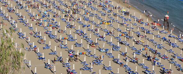 molti ombrelloni chiusi sulla spiaggia