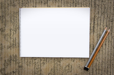 Notebook with pencil on concrete background