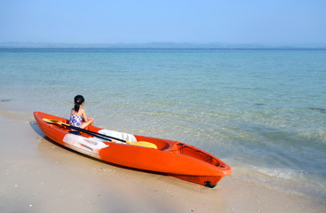young asian girl in swimming suit sitting on orange kayak with yellow paddle on a sandy beach