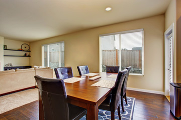 Dining area with wooden table set and leather chairs.