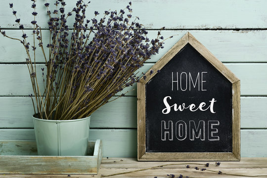 text home sweet home in a house-shaped signboard