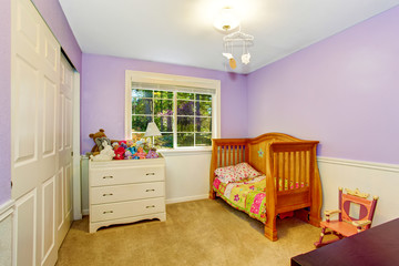 Kids bedroom interior in purple tones with lots of toys