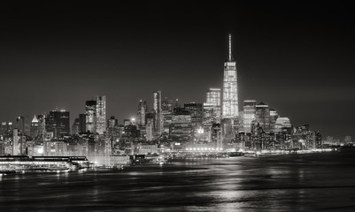 Fotomurales - Skyscrapers of New York City Financial District illuminated at night. Aerial panoramic view of Lower Manhattan and the Hudson River in Black & White