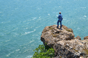 Gray haired man on a rock high above the blue sea