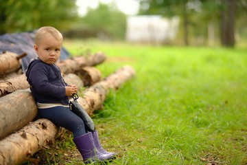Little child sits on logs in village. Russian rural view