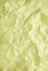 A full page of scrunched up pastel yellow wrapping paper texture