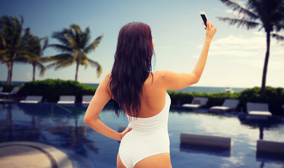 young woman taking selfie with smartphone on beach