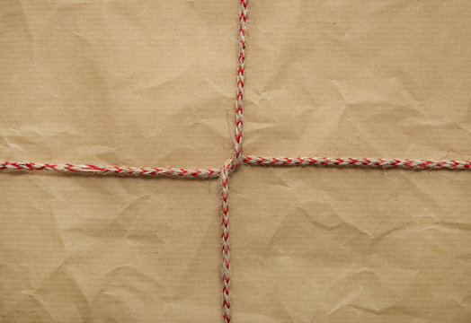A full page of creased brown parcel paper texture with red bakers twine tied around it