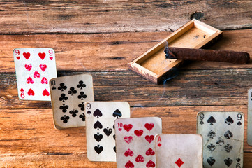 Playing cards and cigar on wooden table