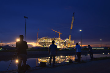 Landscape photographers shooting images photography at construction oil and gas rig plant at twilight.