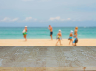 Empty wood table on beach sea summer day and water blue sand and people blurred background