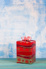 Christmas present box over blue wooden background, above view.