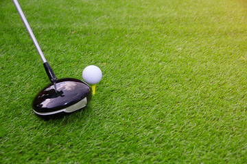 Golf club and golf ball on grass swing shot in the summer