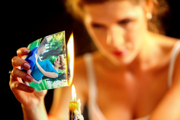 Uhappy girl burn love photos. Love is gone. Model on photo is the same image in the picture.