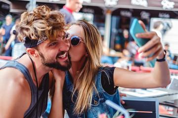 Girl kissing boyfriend while taking selfie