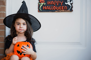 Pretty little girl in witch hat with pumpkin bag looking at camera