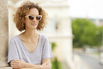 Confident young woman in the city. Close-up of a woman relaxing outdoor in a perfect sunny day.