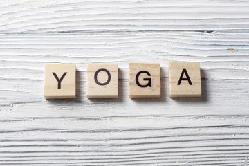 text of YOGA on wood abc cubes