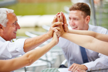 Hands of business team giving high five