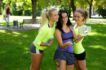 Three sporty females doing selfie in a park.