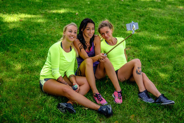 Three  sporty females sitting on a lawn and doing selfie.