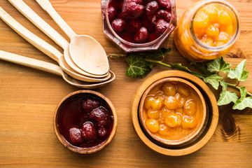 Strawberry and Yellow Cherry Jam on a wooden surface.