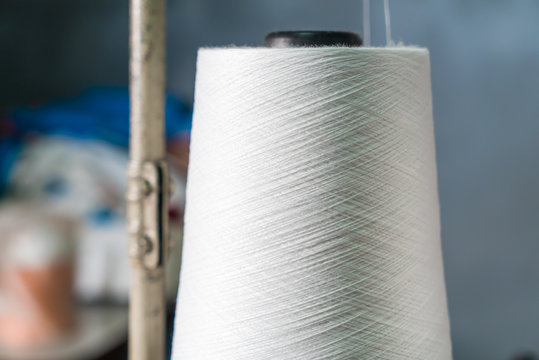 Obbin of white thread on sewing machine in the factory