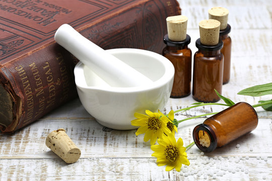 homeopathic arnica pills on wooden background