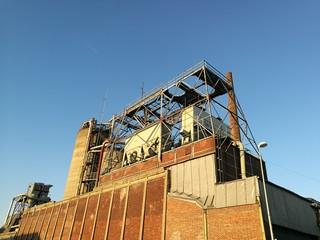 Stillgelegte alte Fabrik mit rotbrauner Backsteinmauer im Licht der untergehenden Sonne am Hafen von Münster in Westfalen