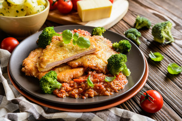 Piccata - fried pork cutlets stuffed with smoked ham slices coated in cheese and eggs served with tomato sauce, steamed broccoli and boiled potatoes